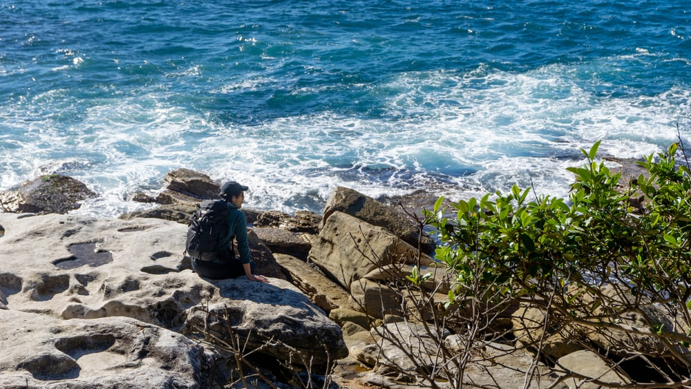 man in black jacket sitting on rock near body of water during daytime