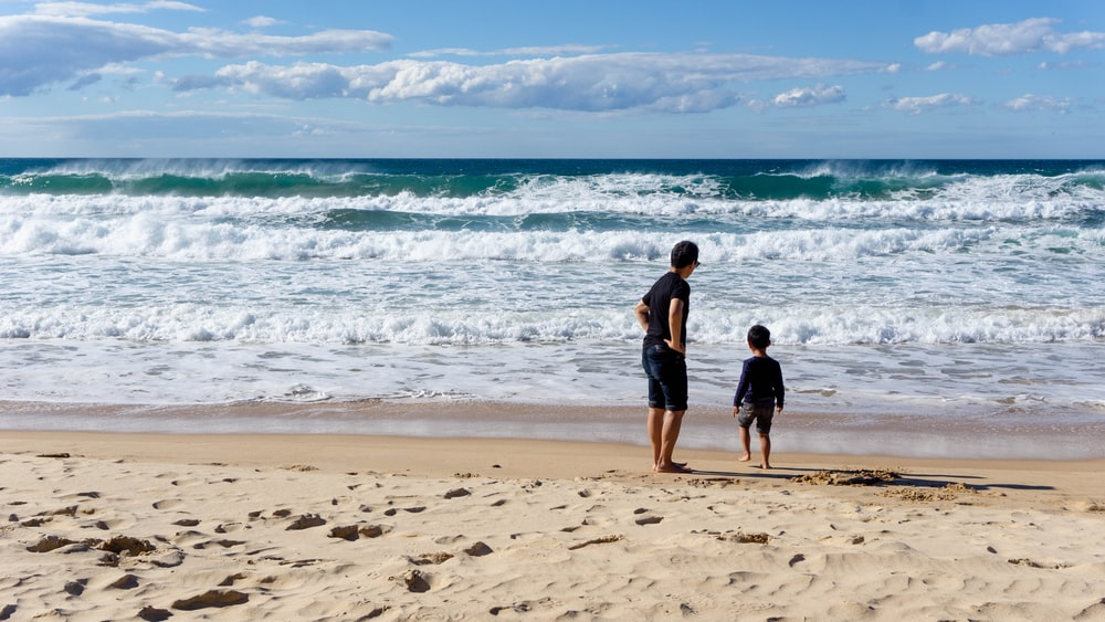 2 men standing on beach during daytime