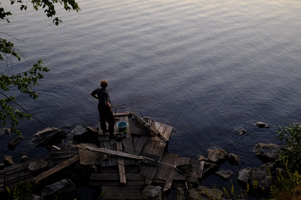 man in black shirt standing on brown wooden boat on body of water during daytime