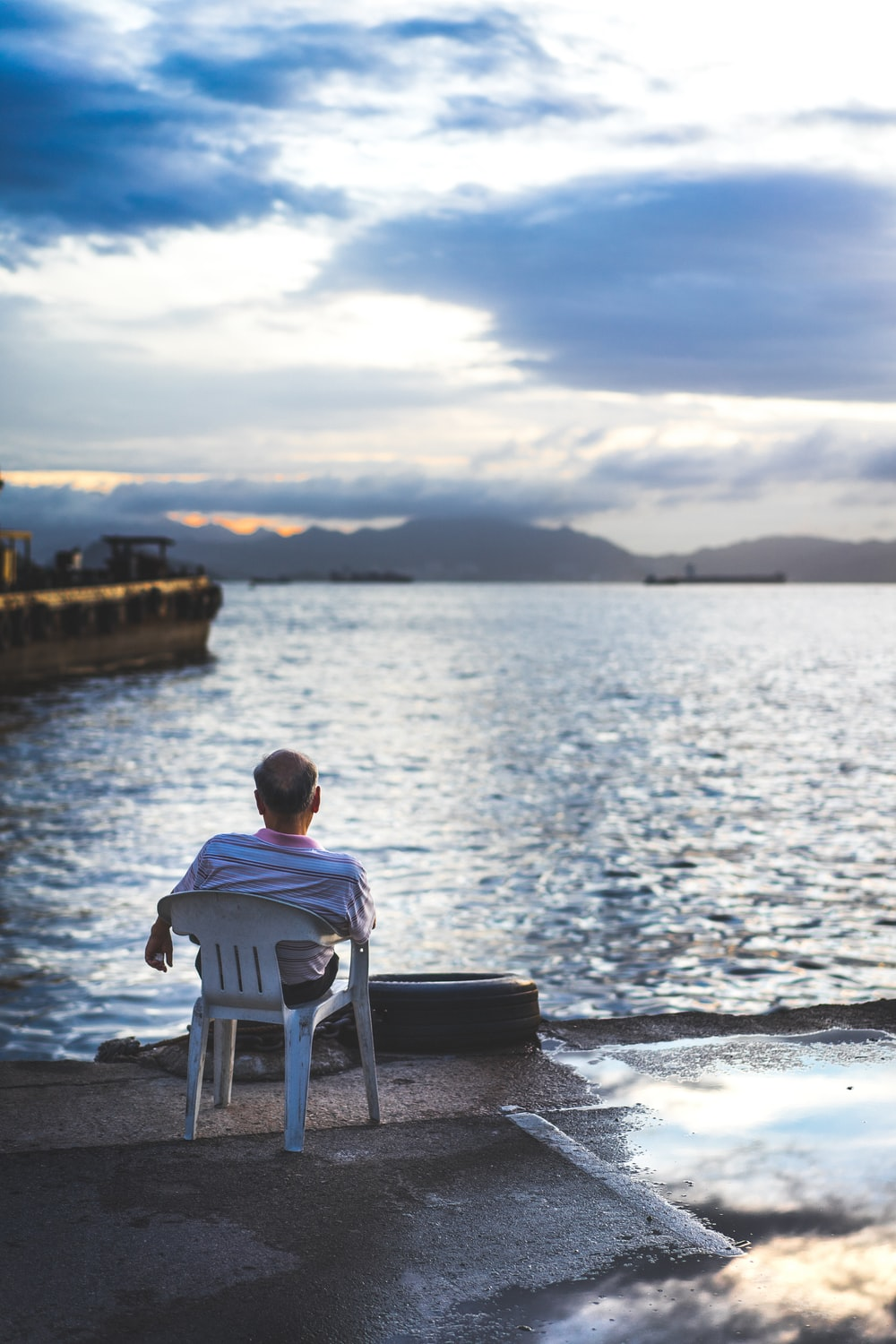 man in white shirt sitting on white plastic chair near body of water during daytime