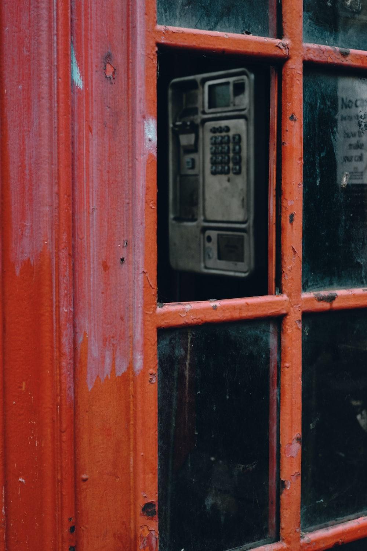 black telephone booth on red wooden door