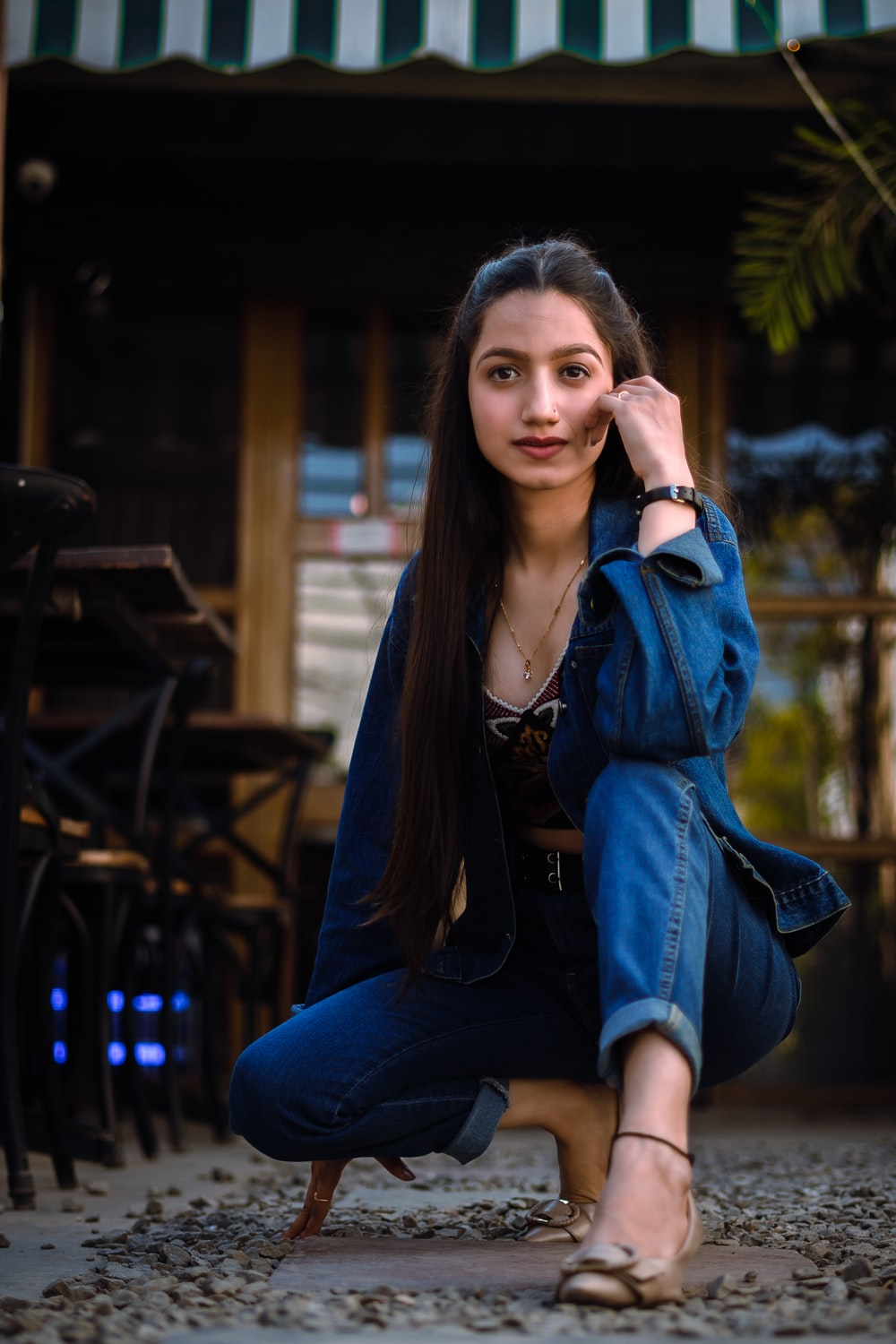 woman in blue denim jacket and blue denim jeans sitting on brown wooden bench