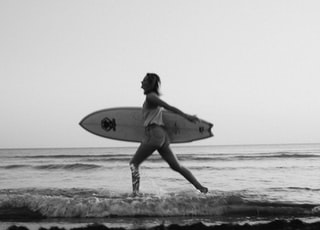 grayscale photo of woman holding surfboard on beach