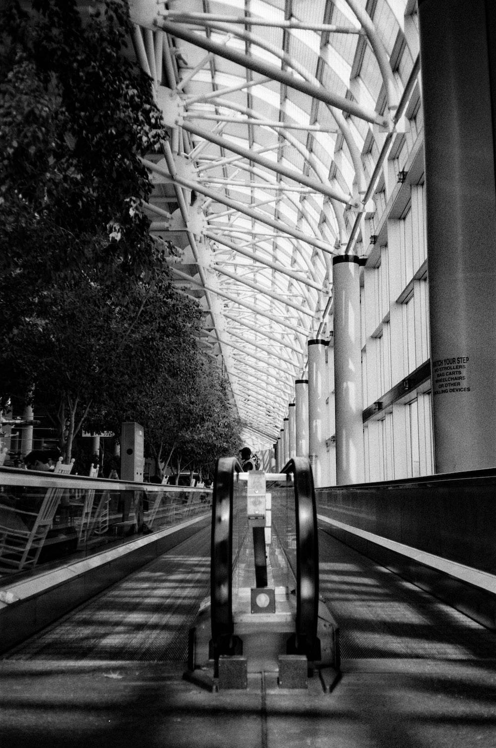 grayscale photo of a man walking on a bridge