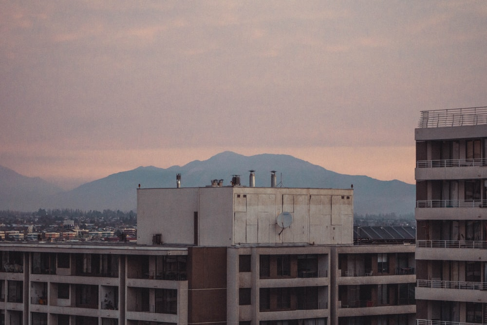 white concrete building near mountain during daytime