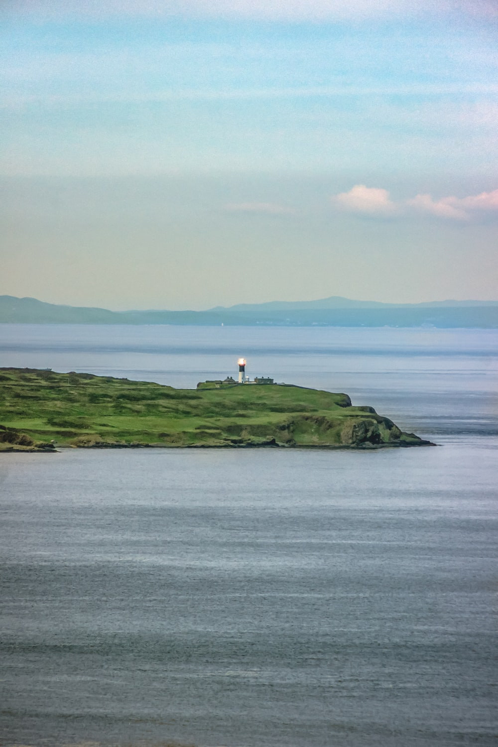 white lighthouse on green grass covered hill by the sea under white clouds during daytime