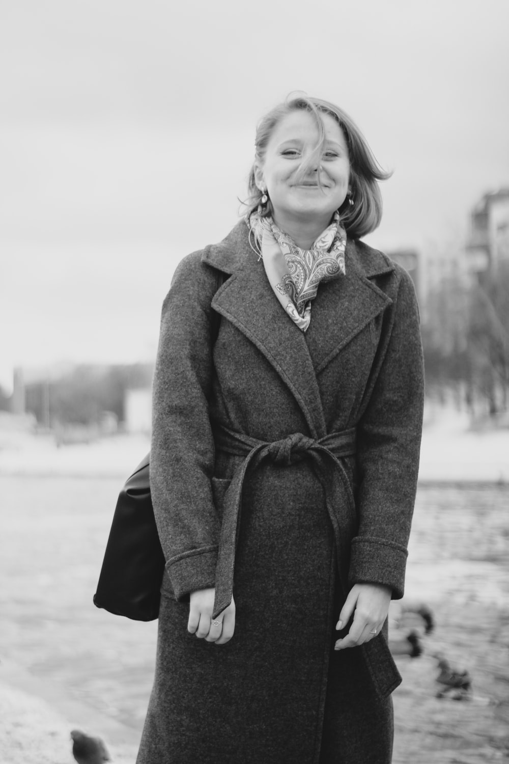 grayscale photo of woman in coat smiling