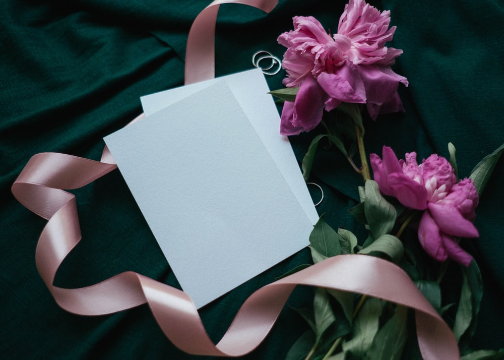 white and pink greeting card on green textile