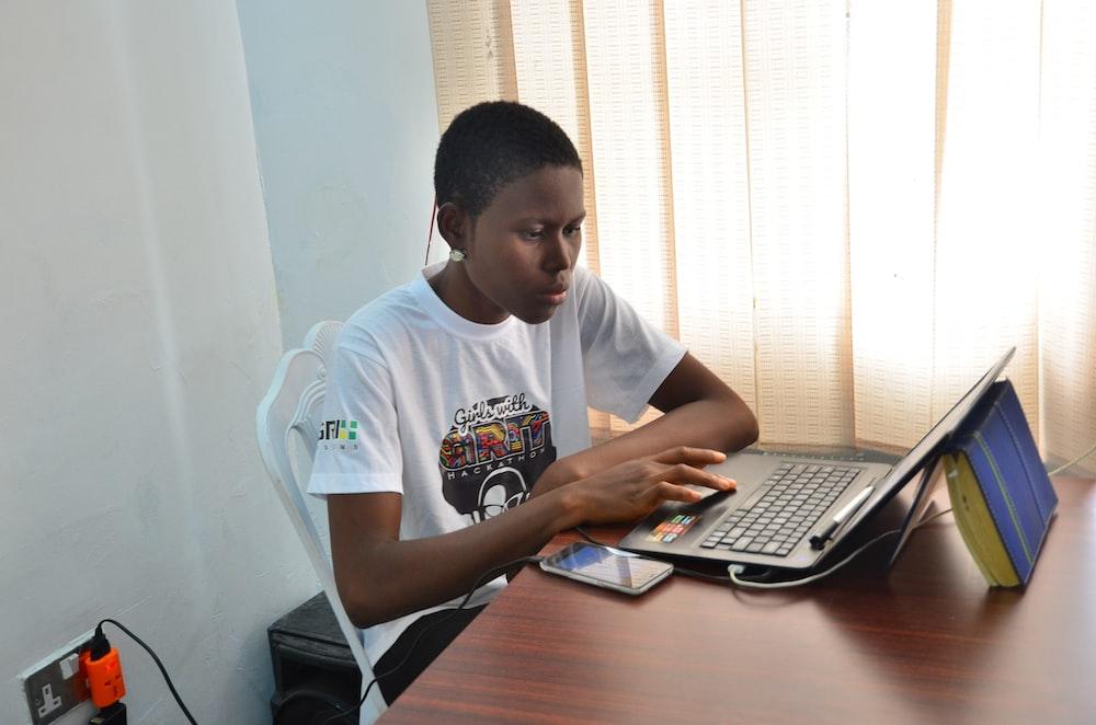 man in white crew neck t-shirt using black laptop computer