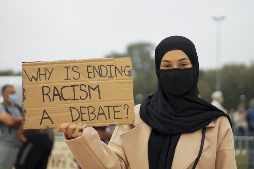 woman in black hijab holding brown wooden welcome to the beach signage