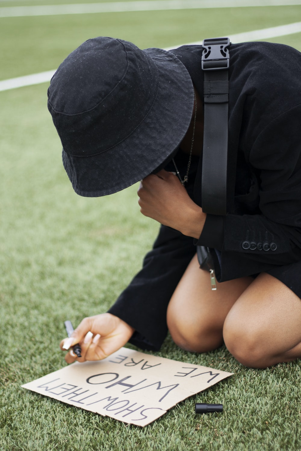 woman in black hat and black t-shirt sitting on green grass field during daytime