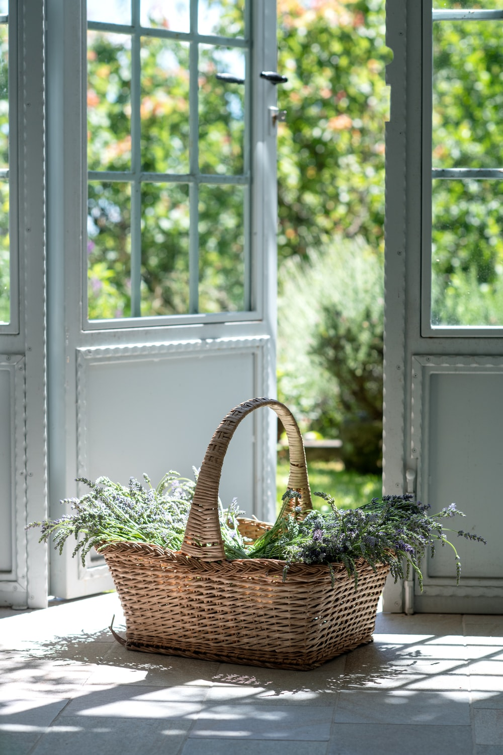 brown woven basket on white wooden window