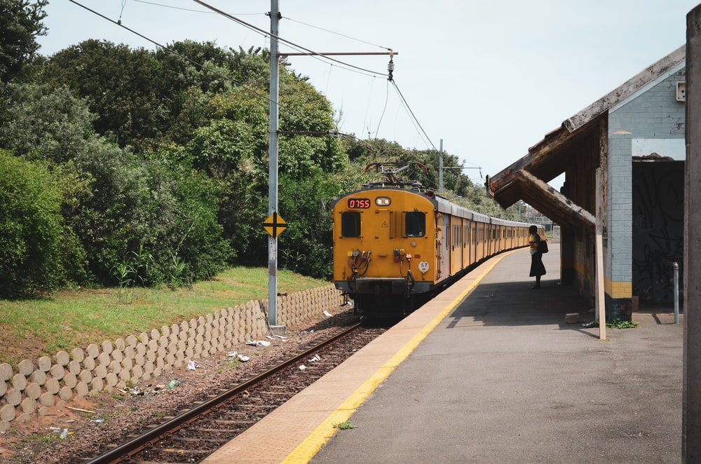 yellow train on rail road during daytime