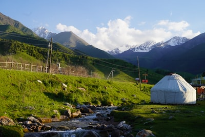 white tent on green grass field near mountain during daytime kyrgyzstan teams background