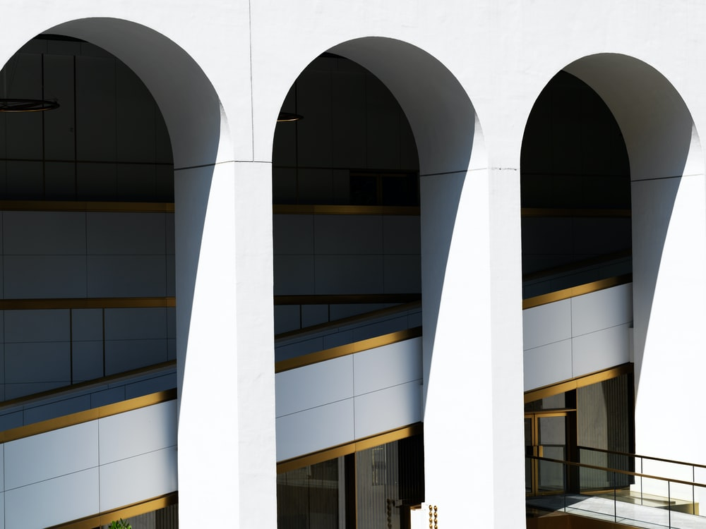 white concrete pillar near glass window