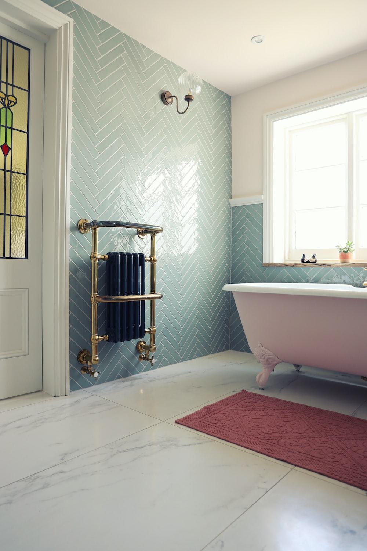 white ceramic bathtub near white bathtub