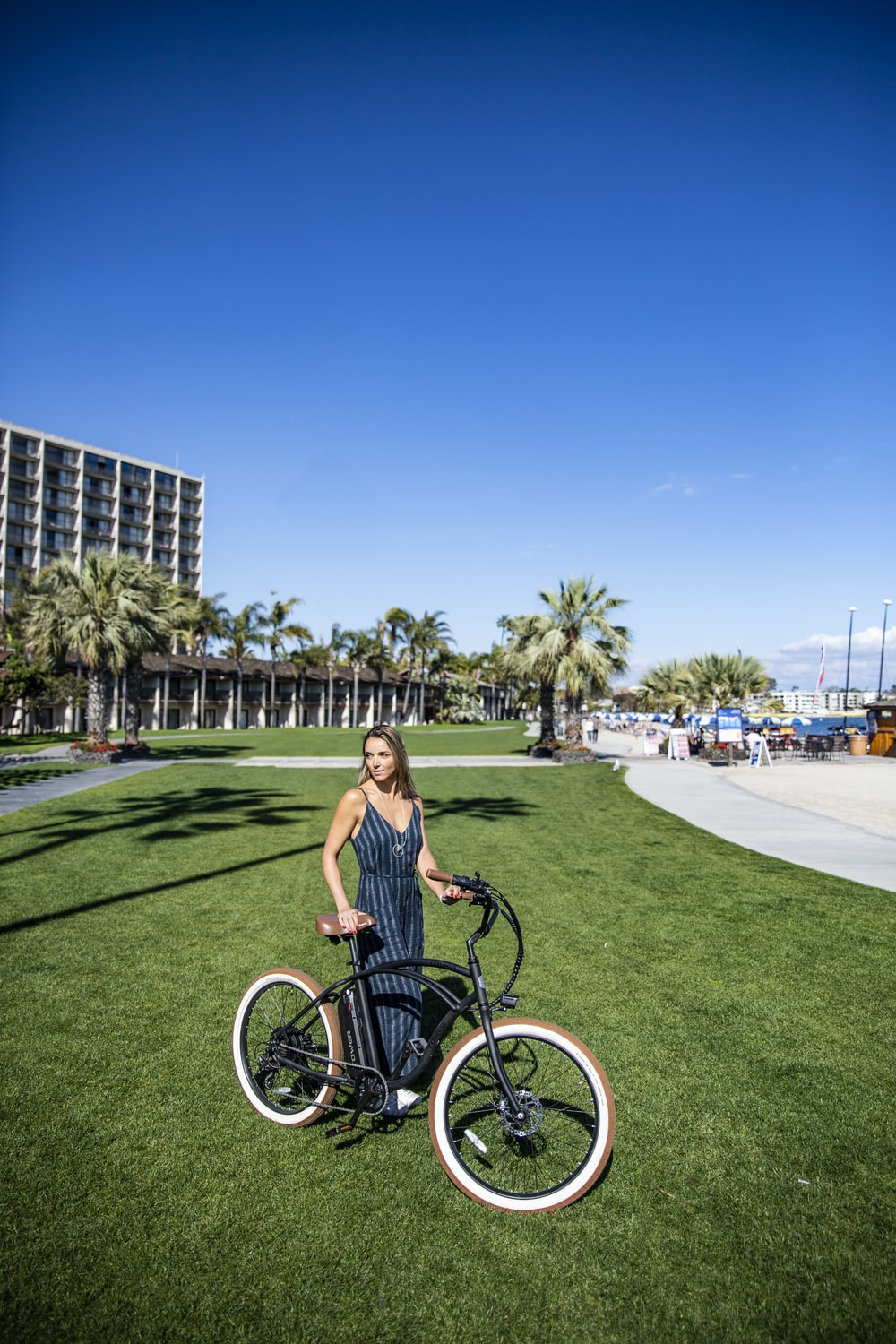 woman in black tank top riding on bicycle on green grass field during daytime