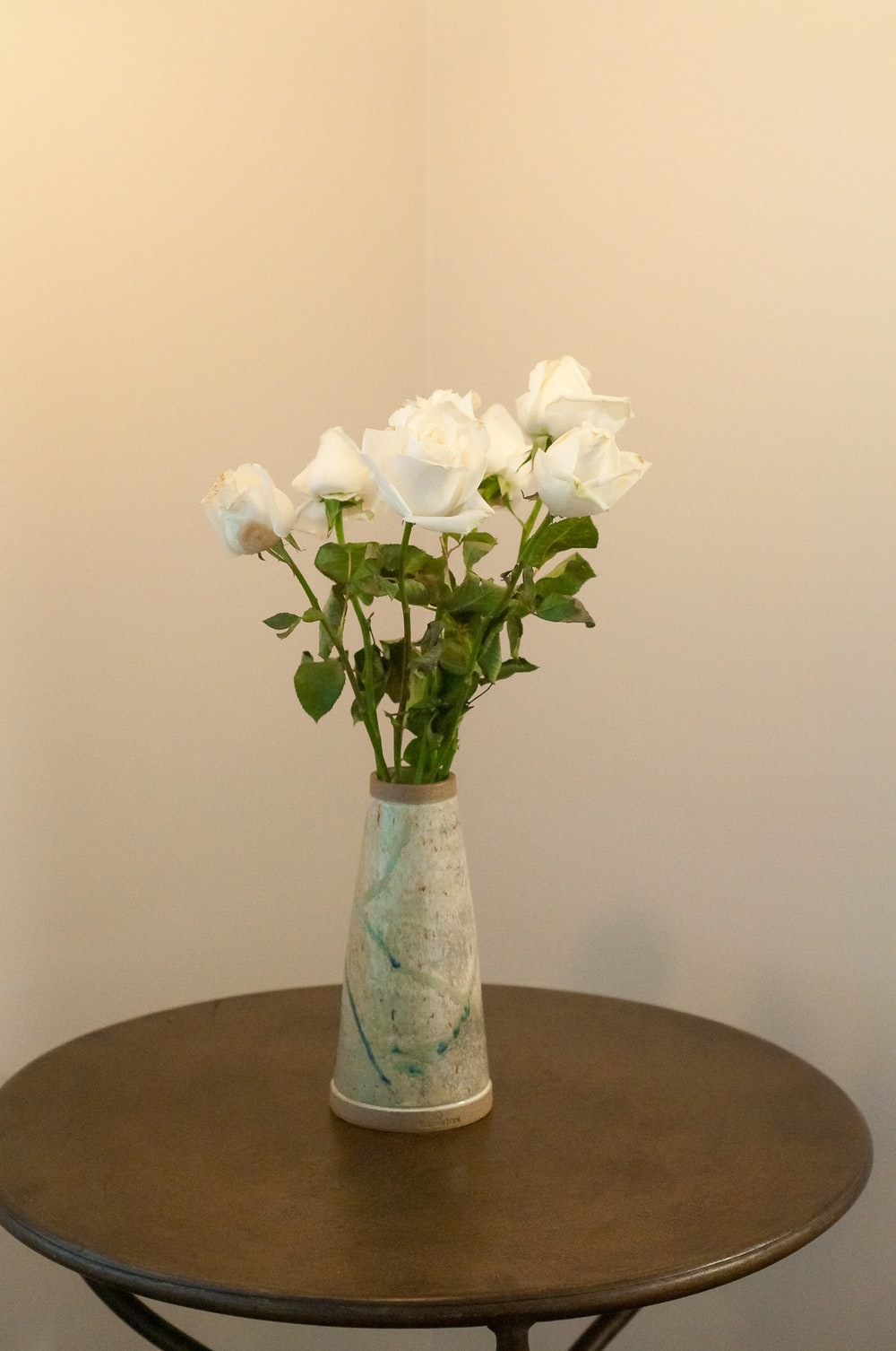 white flowers in blue glass vase