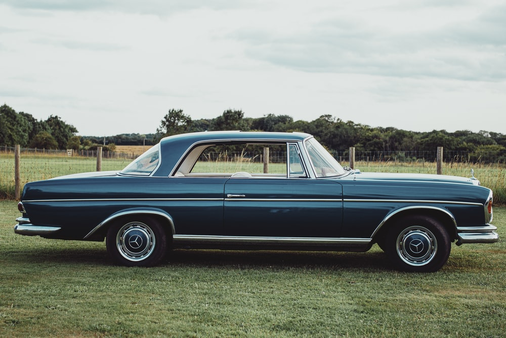 blue classic car on green grass field during daytime