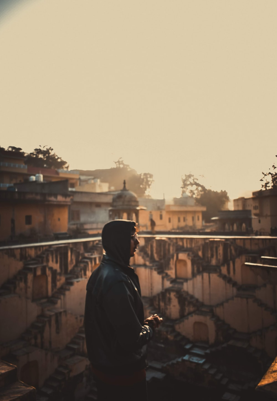 man in black hoodie standing on top of building during daytime