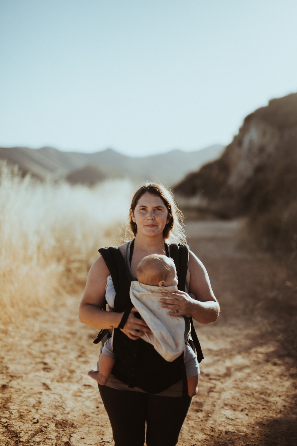 woman in black tank top carrying baby
