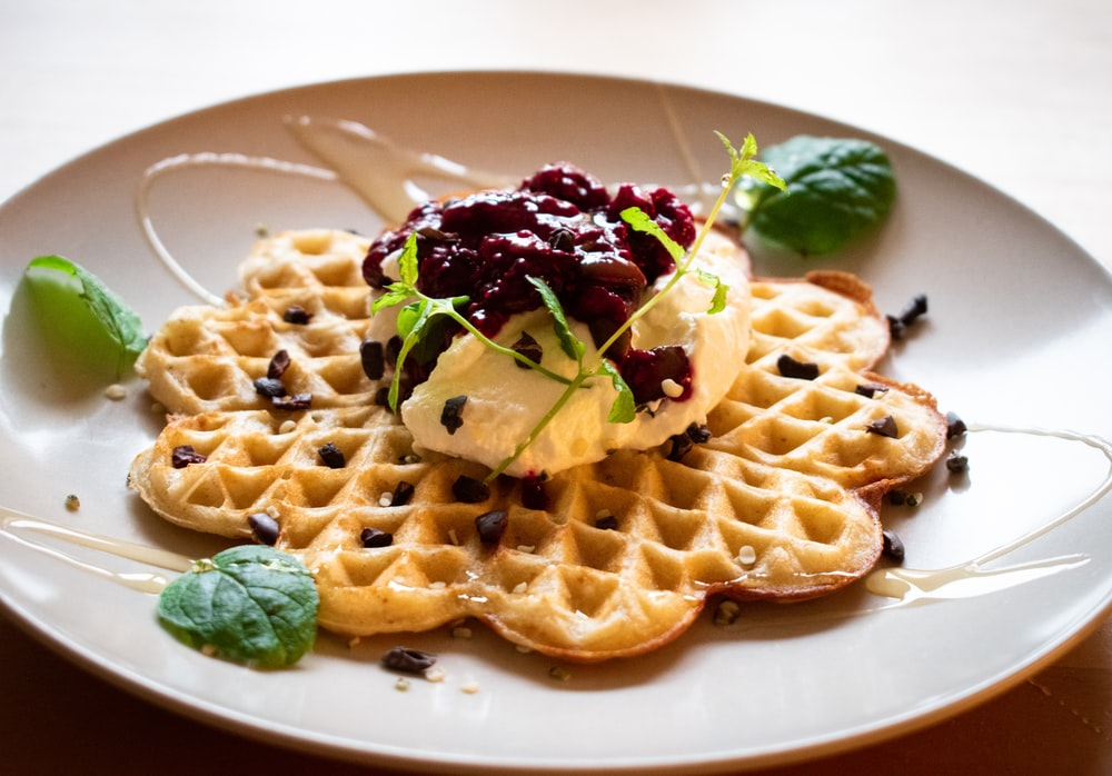 waffle with green and purple vegetable on white ceramic plate