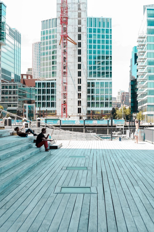 man in black jacket sitting on bench near building during daytime