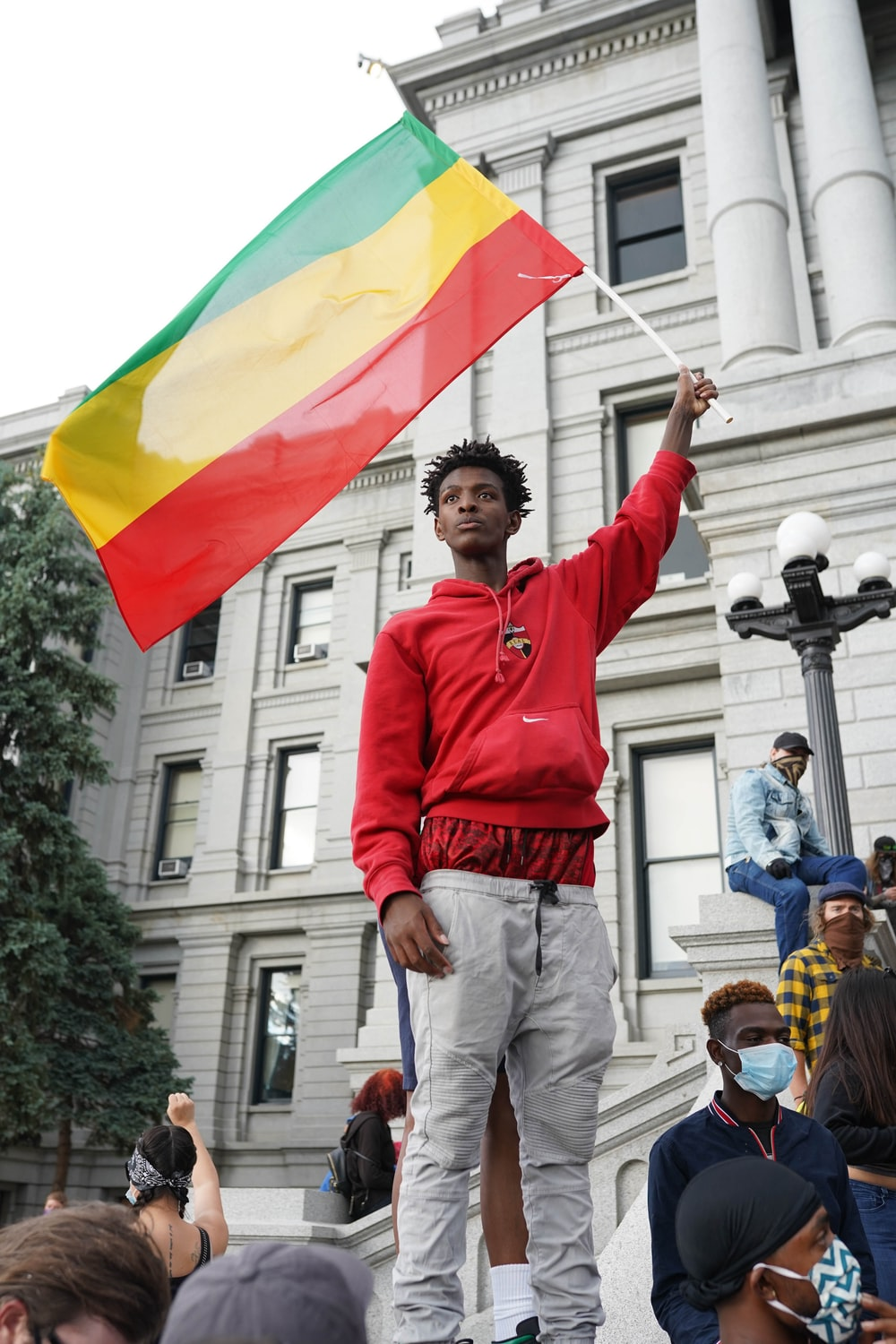 man in red long sleeve shirt holding yellow and red flag