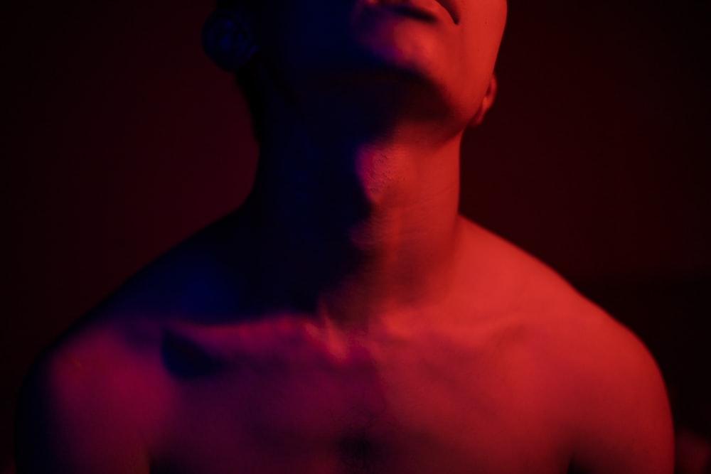 彼の背中に赤い光を持つトップレスの男