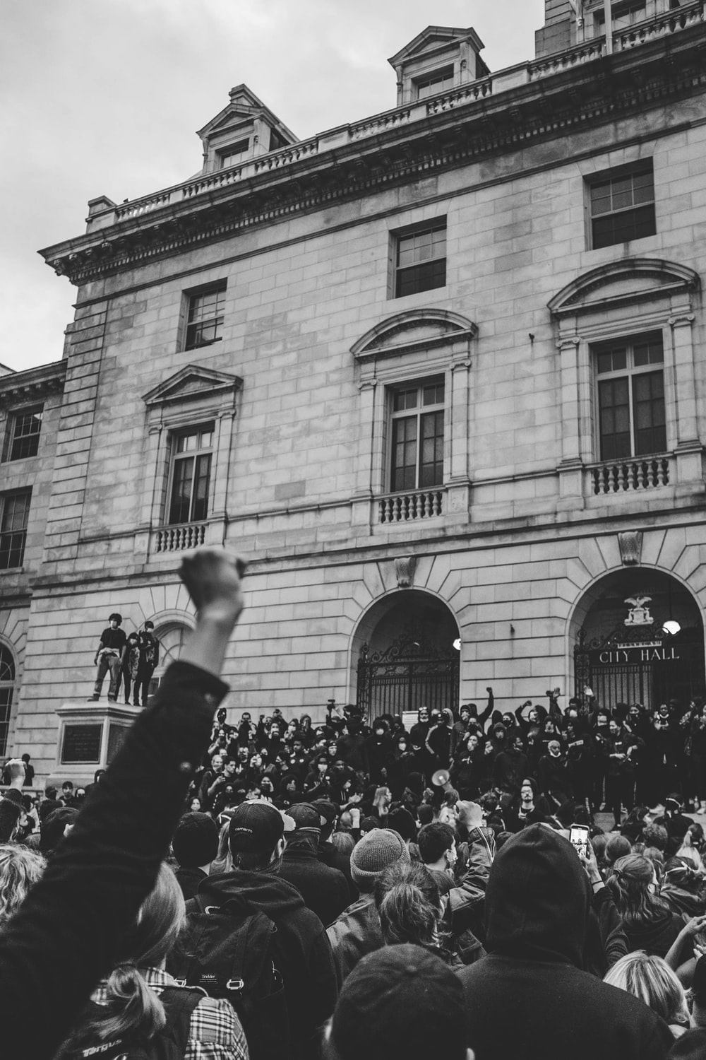 grayscale photo of people in front of building