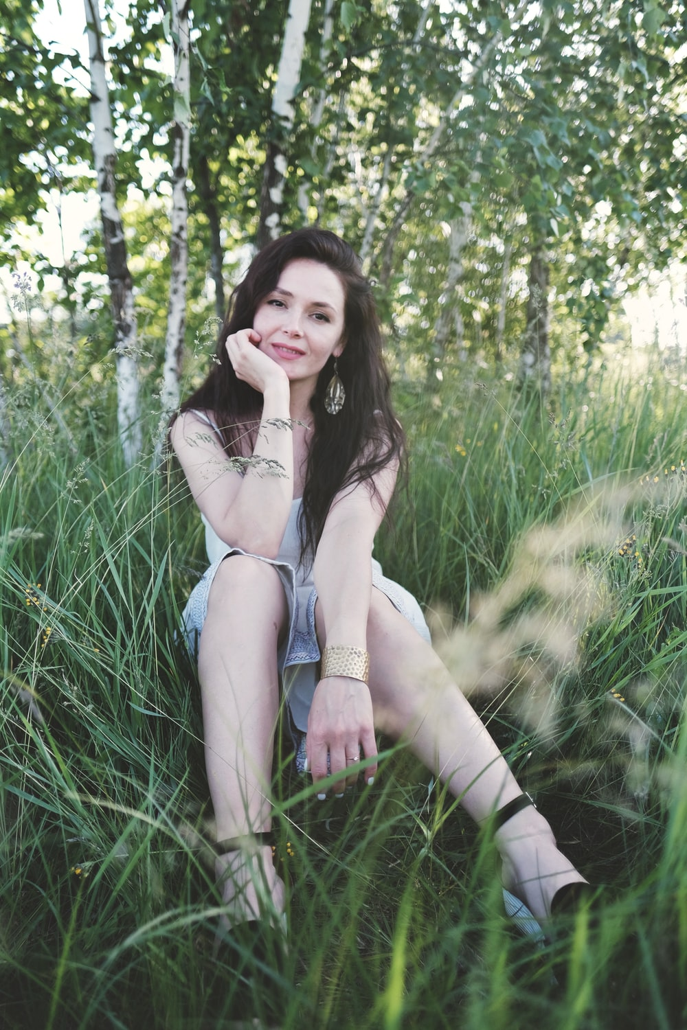woman in white brassiere and blue denim shorts sitting on green grass field