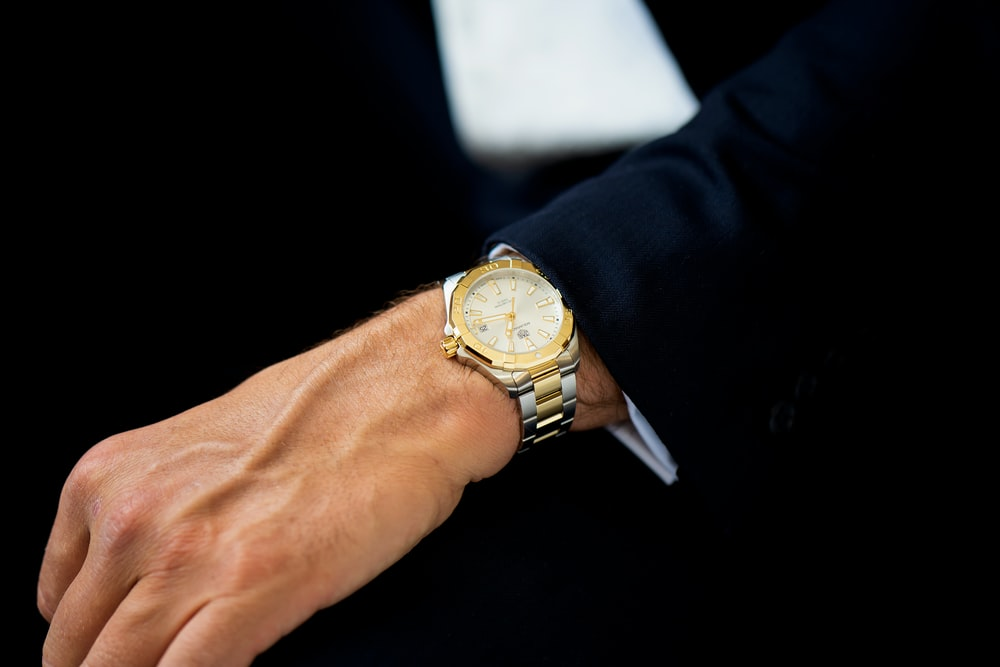 gold and silver round analog watch