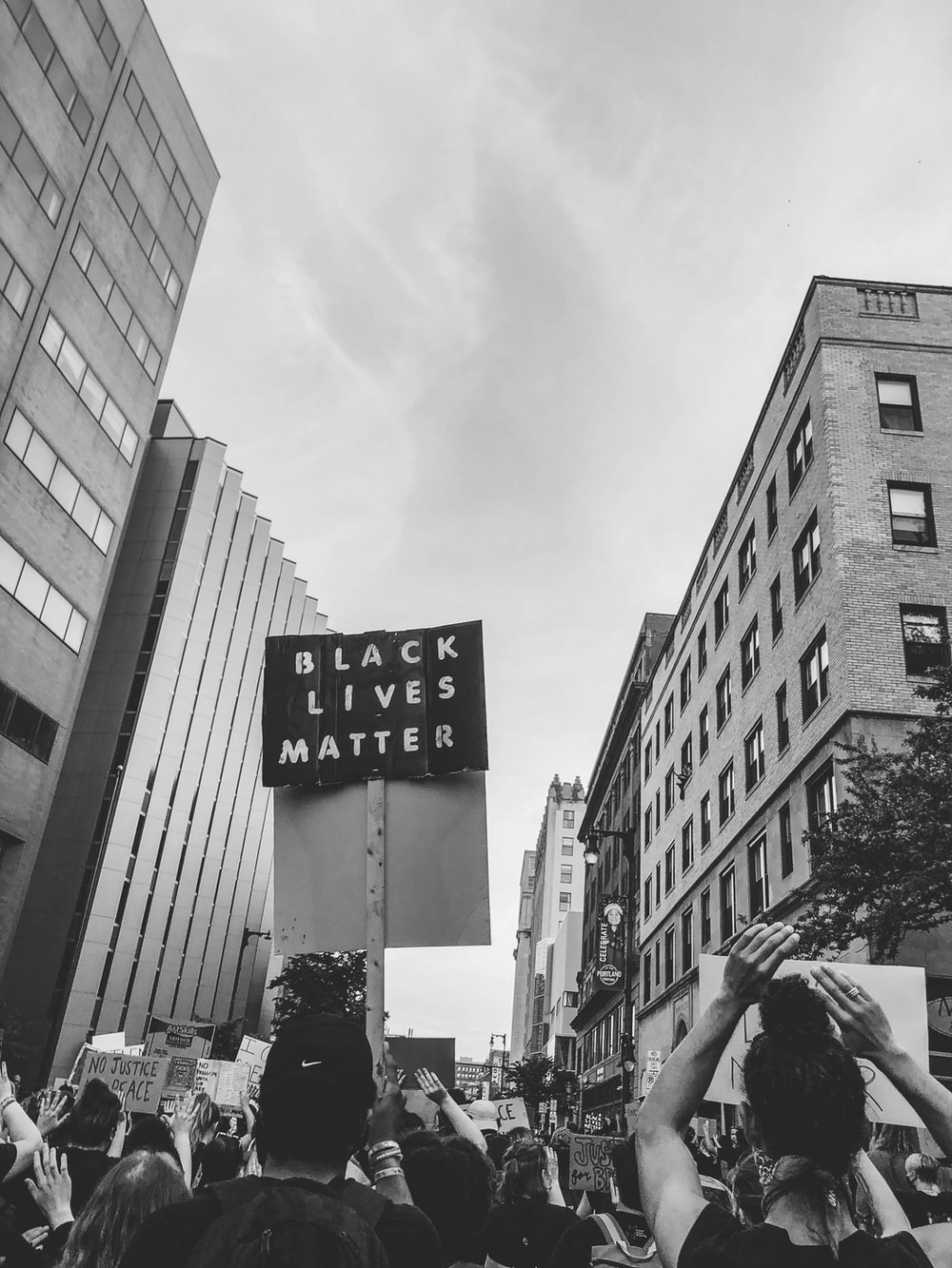 grayscale photo of man in black jacket and black pants walking on pedestrian lane
