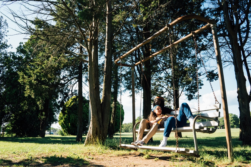 man and woman sitting on swing chair under green leaf trees during daytime