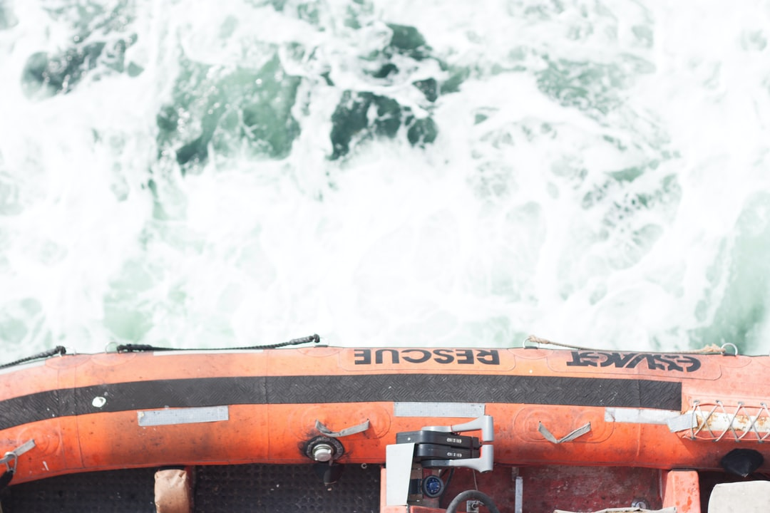 A rescue life raft hangs over the sea.