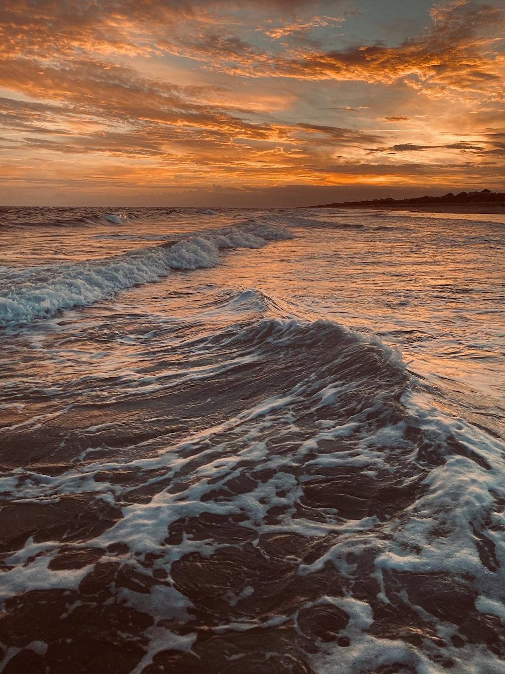 ocean waves crashing on shore during sunset