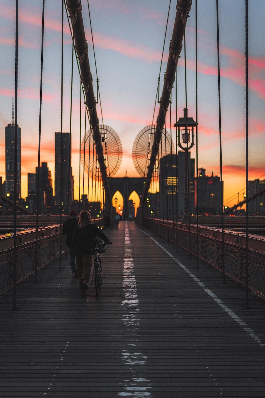 people walking on bridge during sunset