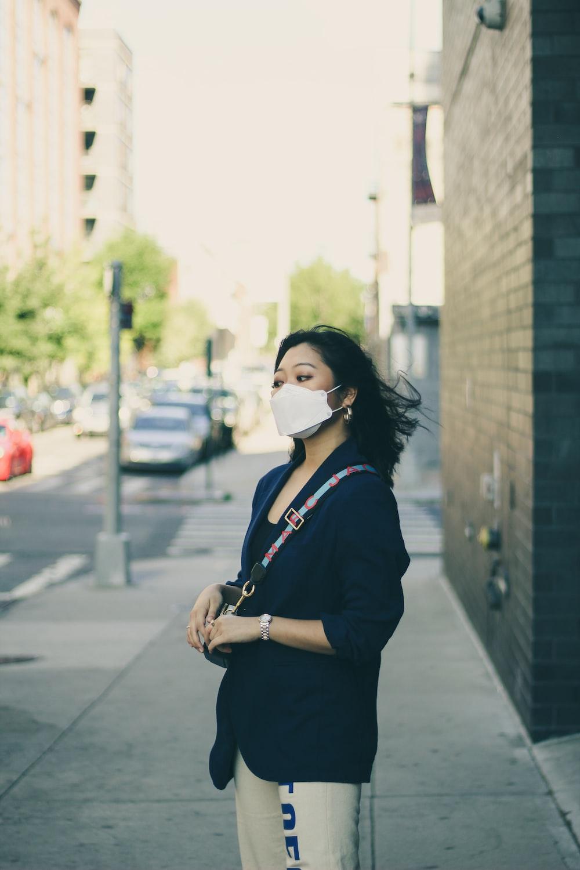 man in black jacket wearing white face mask standing on sidewalk during daytime