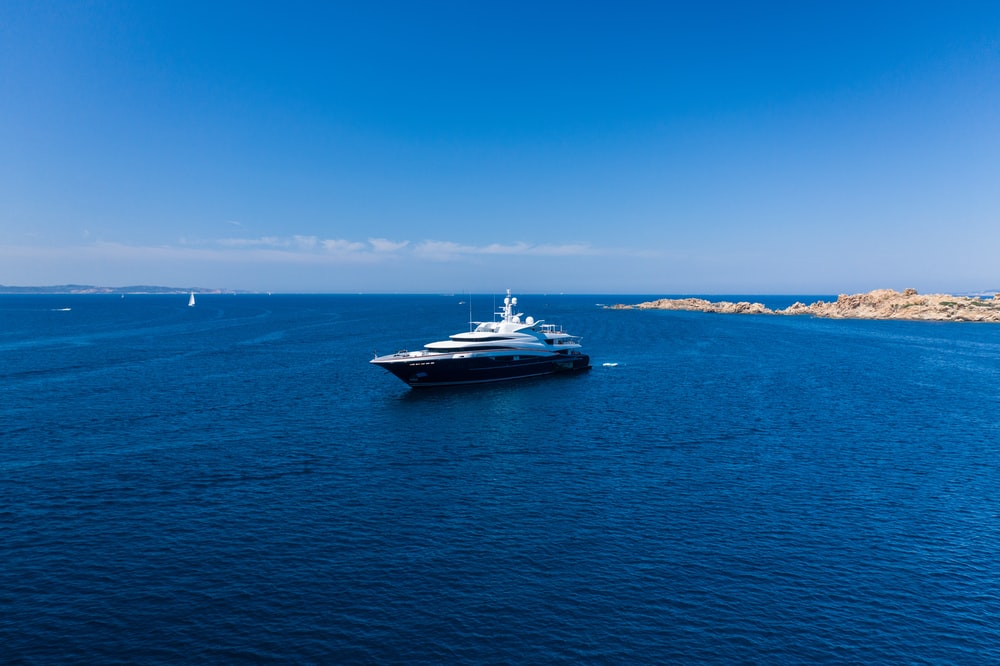 white and black yacht on sea under blue sky during daytime