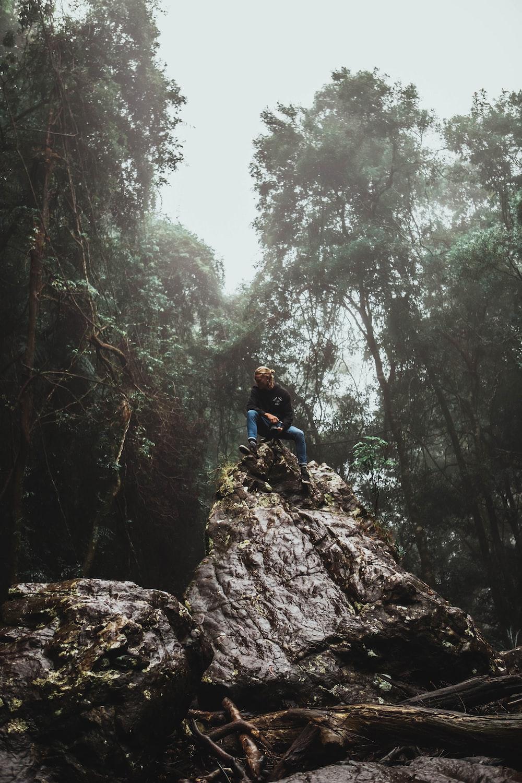 man in blue jacket climbing on brown rocky mountain during daytime