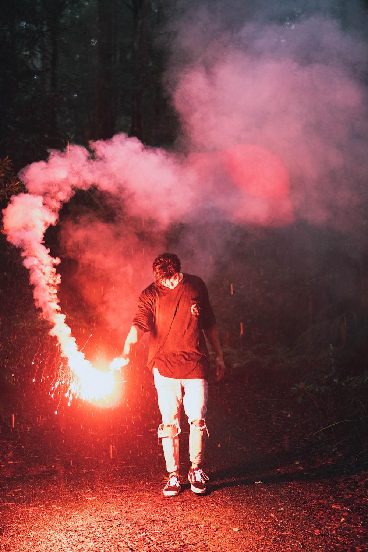 man in black jacket standing on fire