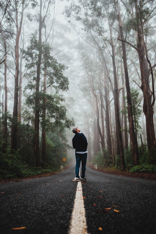man in black jacket standing on road between trees