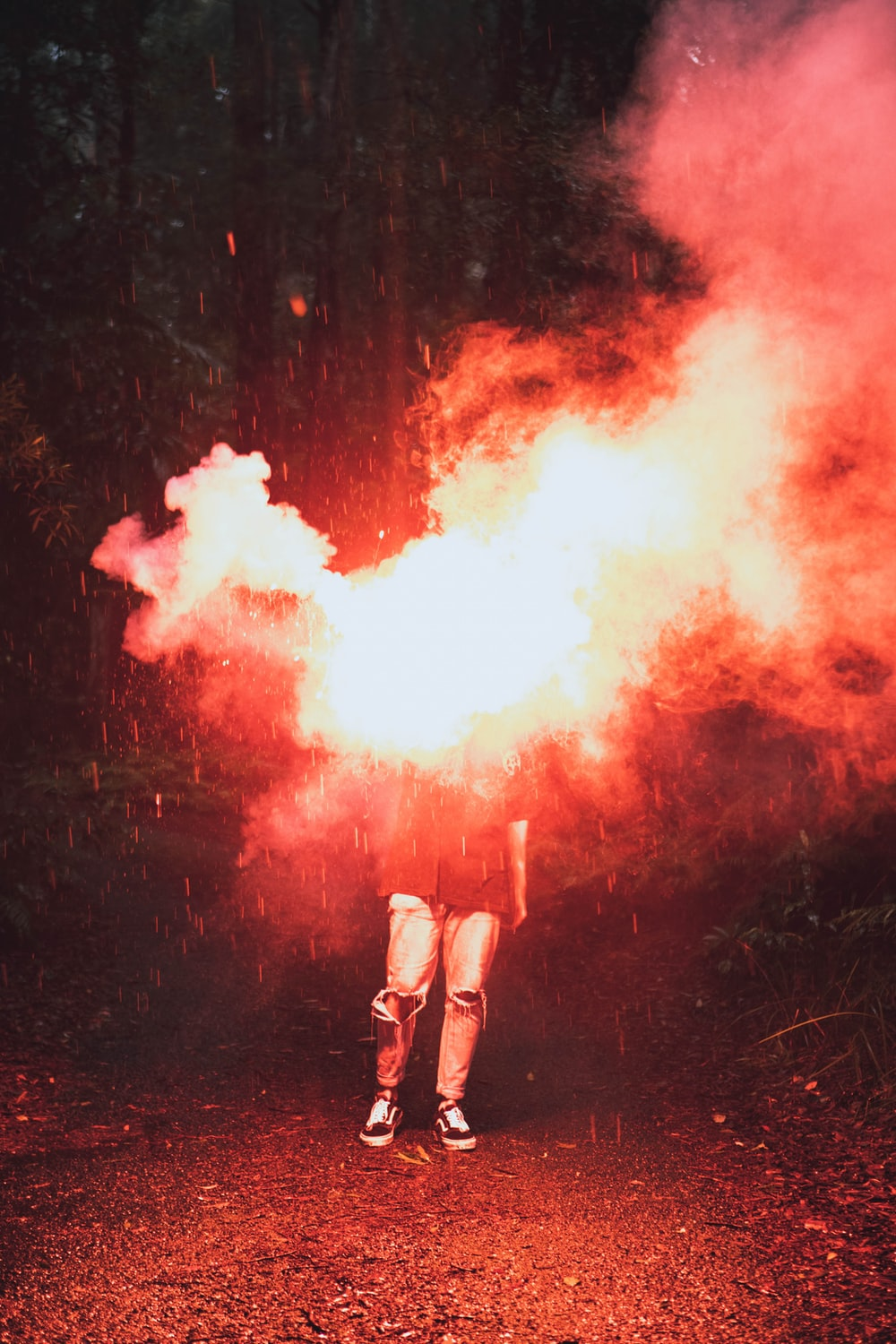 person in white shorts standing on red and white smoke