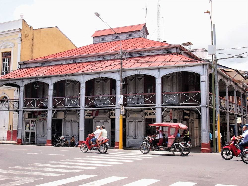 2 men riding motorcycle in front of brown concrete building during daytime