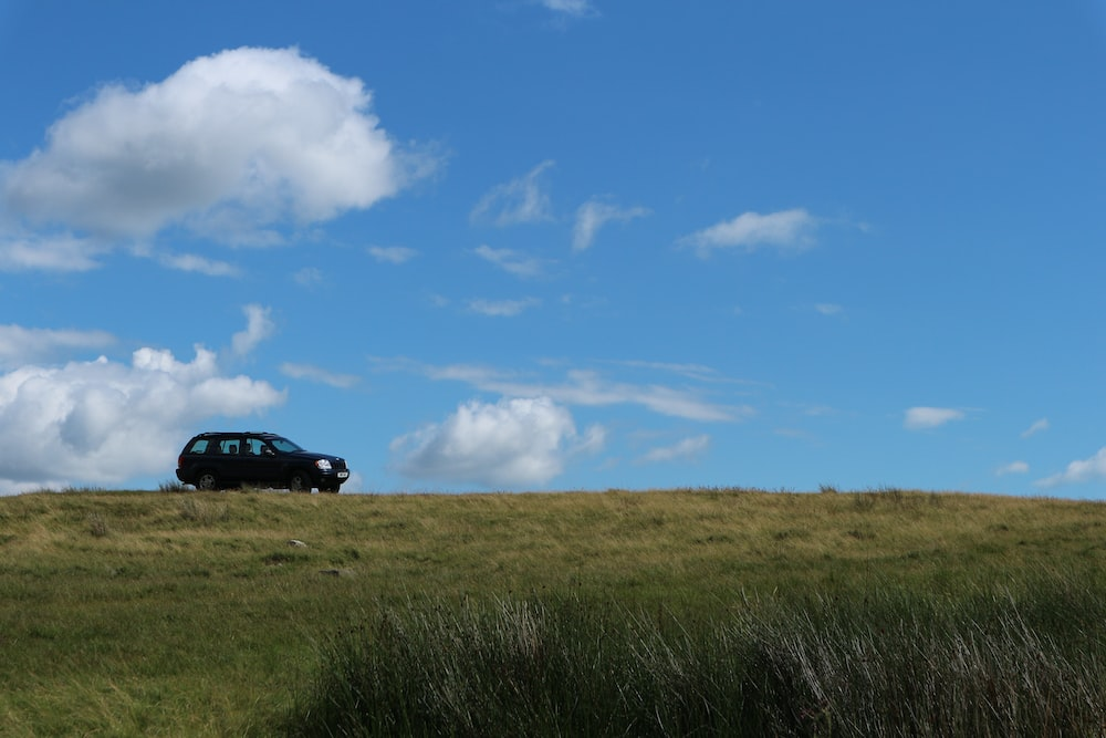 black suv on green grass field under blue sky during daytime