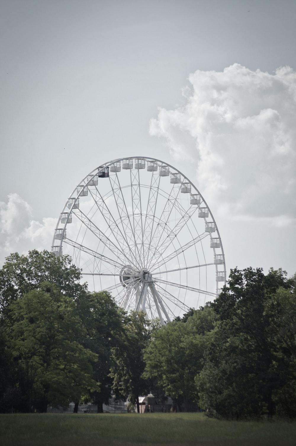white ferris wheel under cloudy sky during daytime