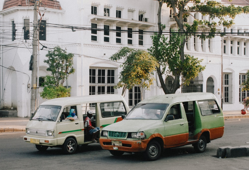 white and green van parked beside white concrete building during daytime