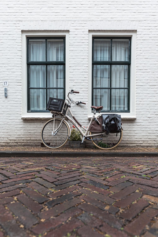 blue city bike parked beside white building