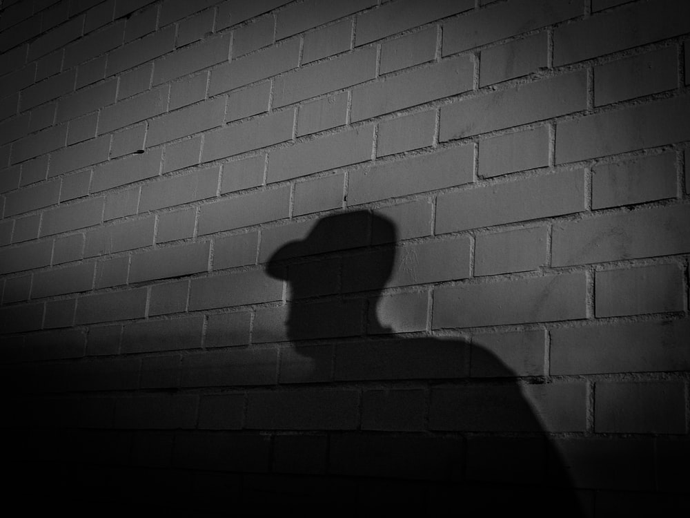 silhouette of man leaning on wall