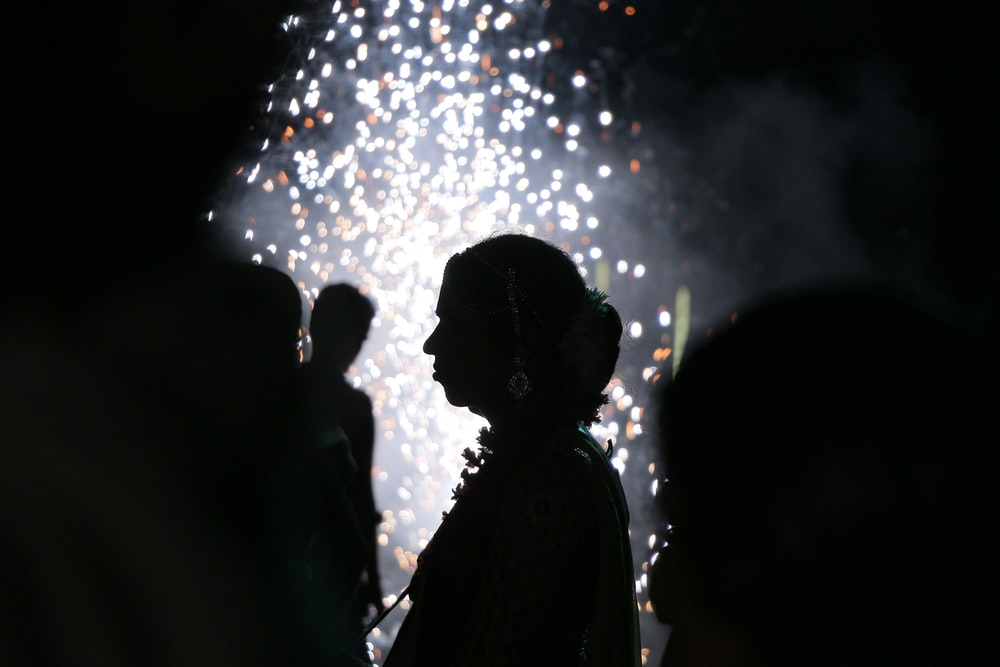 silhouette of people standing under fireworks